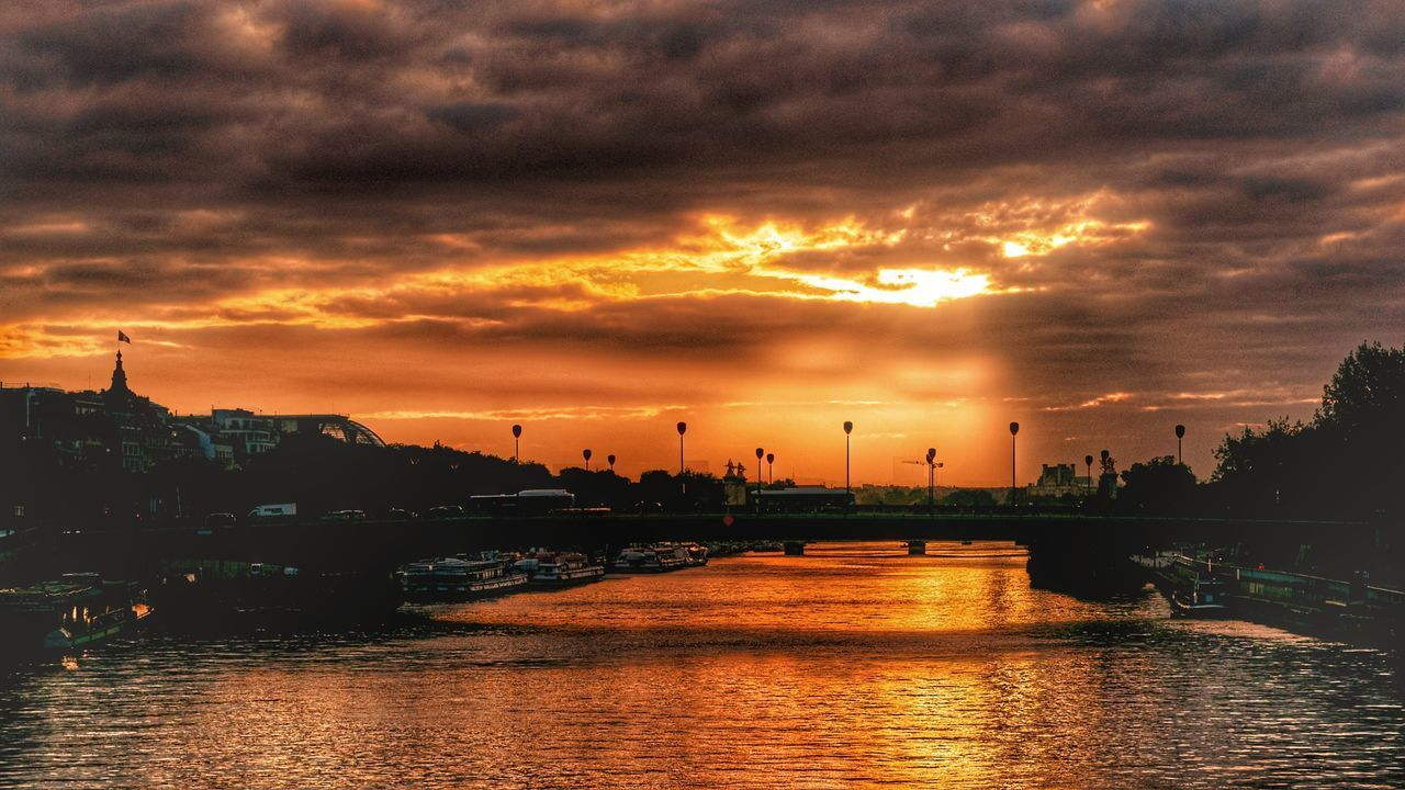 VIEW OF RIVER AGAINST DRAMATIC SKY DURING SUNSET