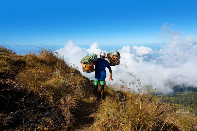 Man carrying baskets on mountain against sky