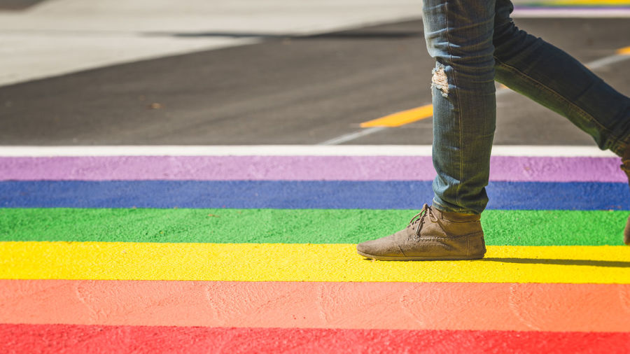 Low Section Of Man Standing On Multi Colored Street