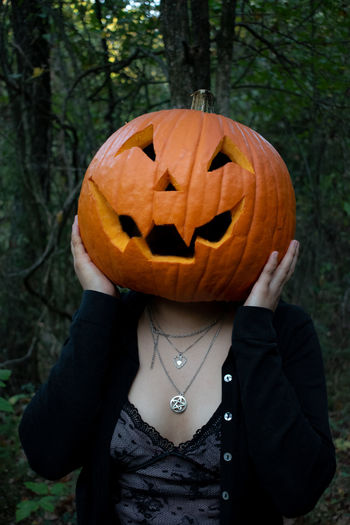 Midsection of person with pumpkin on plant during halloween