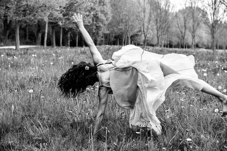 Rear view of woman doing cartwheel on grassy field