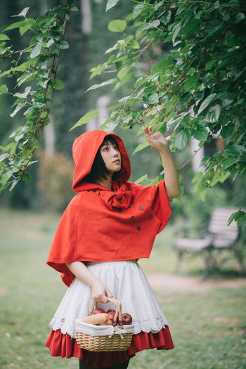 Midsection of woman wearing hat standing against plants