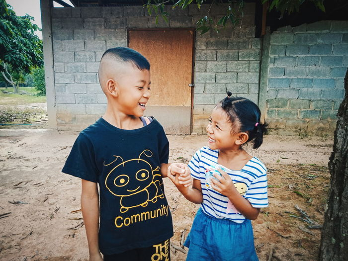 Smiling siblings standing against house