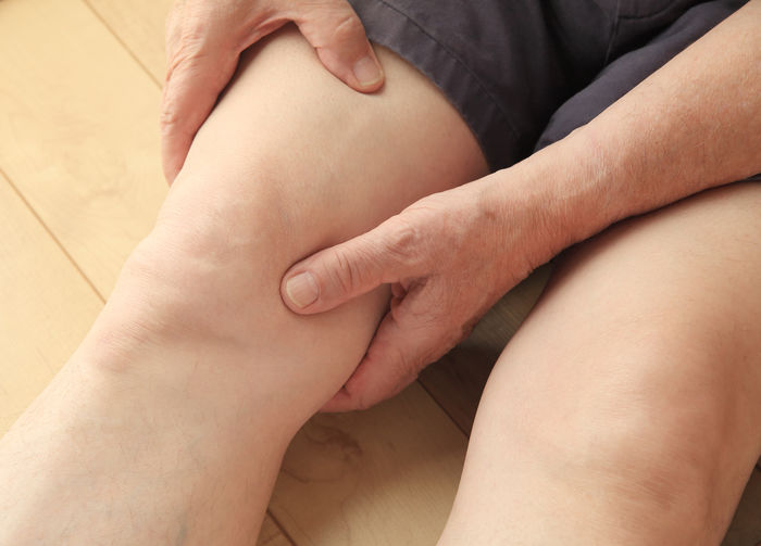 Midsection Of Woman Holding Knee While Sitting On Floor