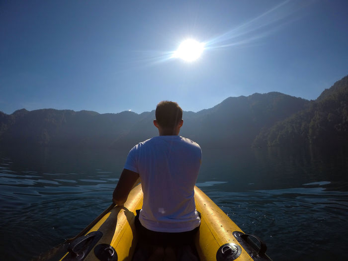 Rear view of man kayaking on river against sky
