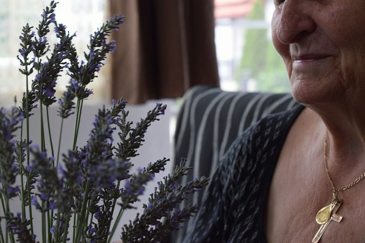 Midsection of smiling senior woman with lavenders at home