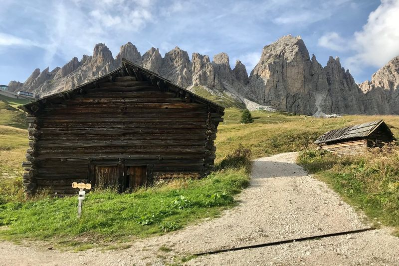 Dolomites, Italy Wood - Material Wood Mountain Mountain Architecture Sky Built Structure No People Day Landscape Nature Environment The Way Forward Beauty In Nature Direction Scenics - Nature Building Exterior Mountain Range Cloud - Sky Field Tranquil Scene