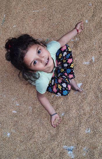 Portrait of cute girl lying on wheat
