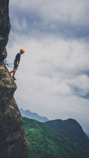 Low angle view of young man rock climbing against cloudy sky