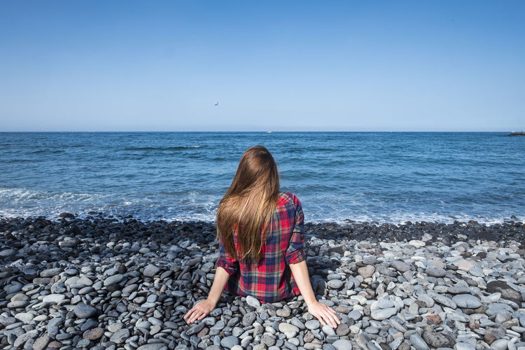 Rear view of woman sitting on rocks at beach against sky