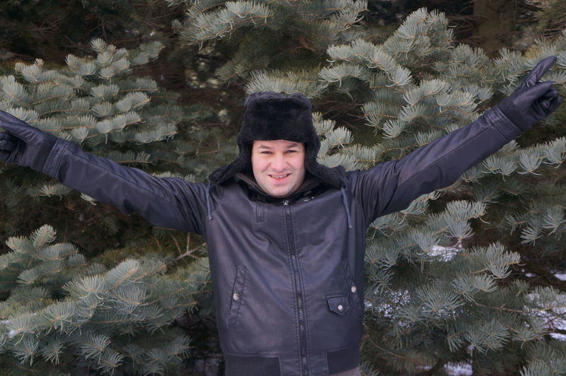 Smiling Man Standing With Arms Raised Against Tree