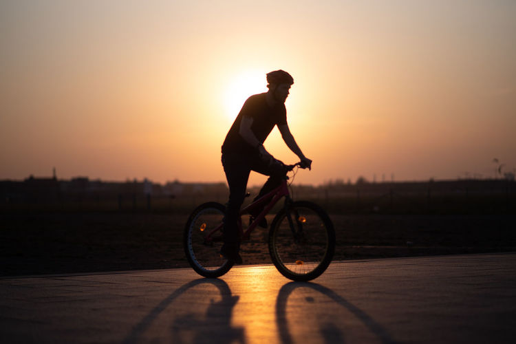 Full length of man cycling on road against sky during sunset