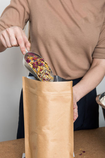 Midsection Of Woman Filling Petals In Paper Bag At Home
