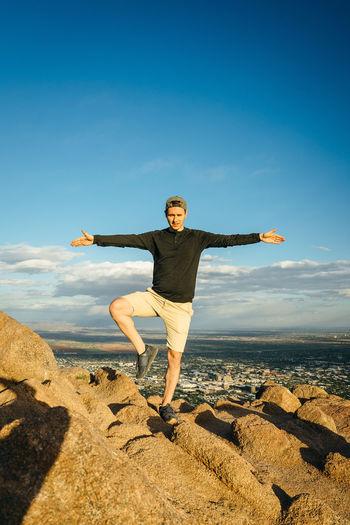 Full length of man standing on one leg over rock against sky
