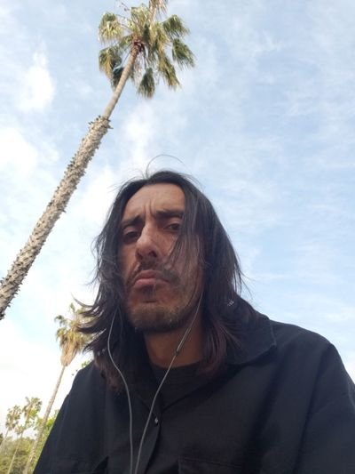Low angle portrait of man against blue sky
