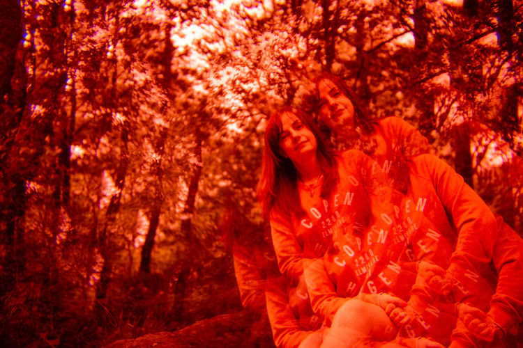 Future Eyes Lens Lomography Prism Prism Art Redscale Red Filter Tree Red Orange Color Young Adult Emotion Plant Young Women Adult Three Quarter Length Autumn Nature People Forest Smiling Women Lifestyles Front View Happiness Outdoors Change Hairstyle Beautiful Woman Couple - Relationship