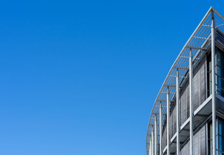 Low angle view of staircase against building against clear blue sky