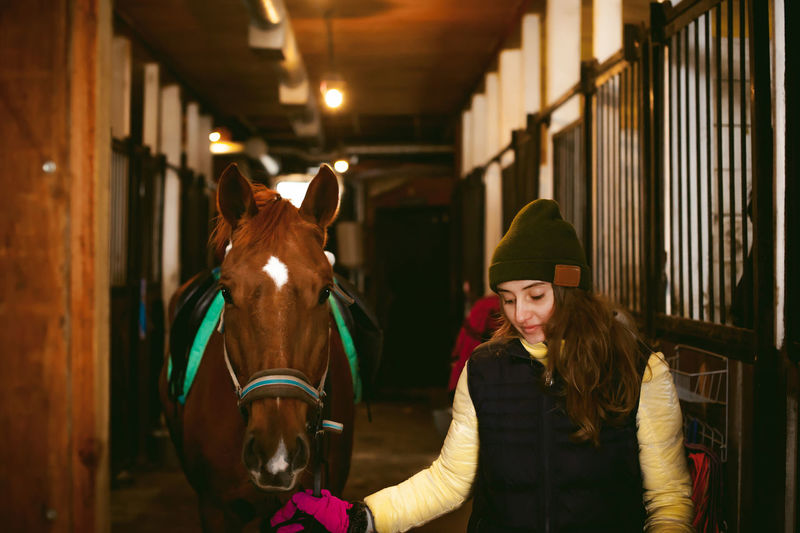 Young woman with horse walking in stable