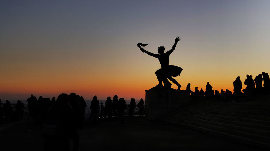 Silhouette people jumping against clear sky during sunset