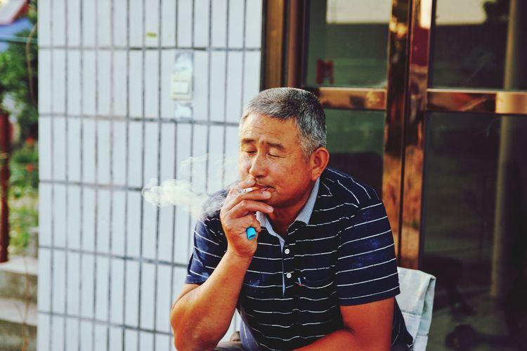 Mid adult man smoking outdoors