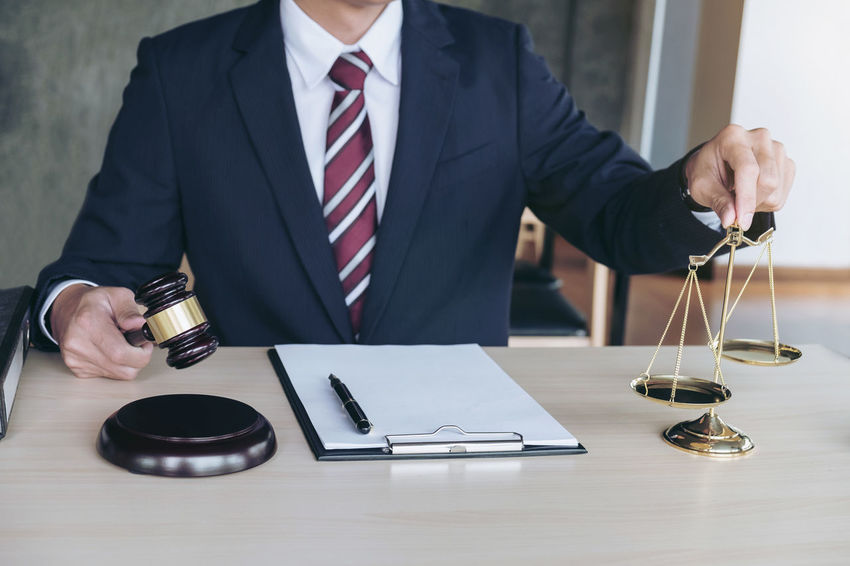 Lawyer Auction Sale Balance Business Businessman Close-up Communication Corporate Business Day Gavel Hammer Indoors  Law Lawyers Men One Person People Real People Scales Sitting Suit Table Technology Wireless Technology Working