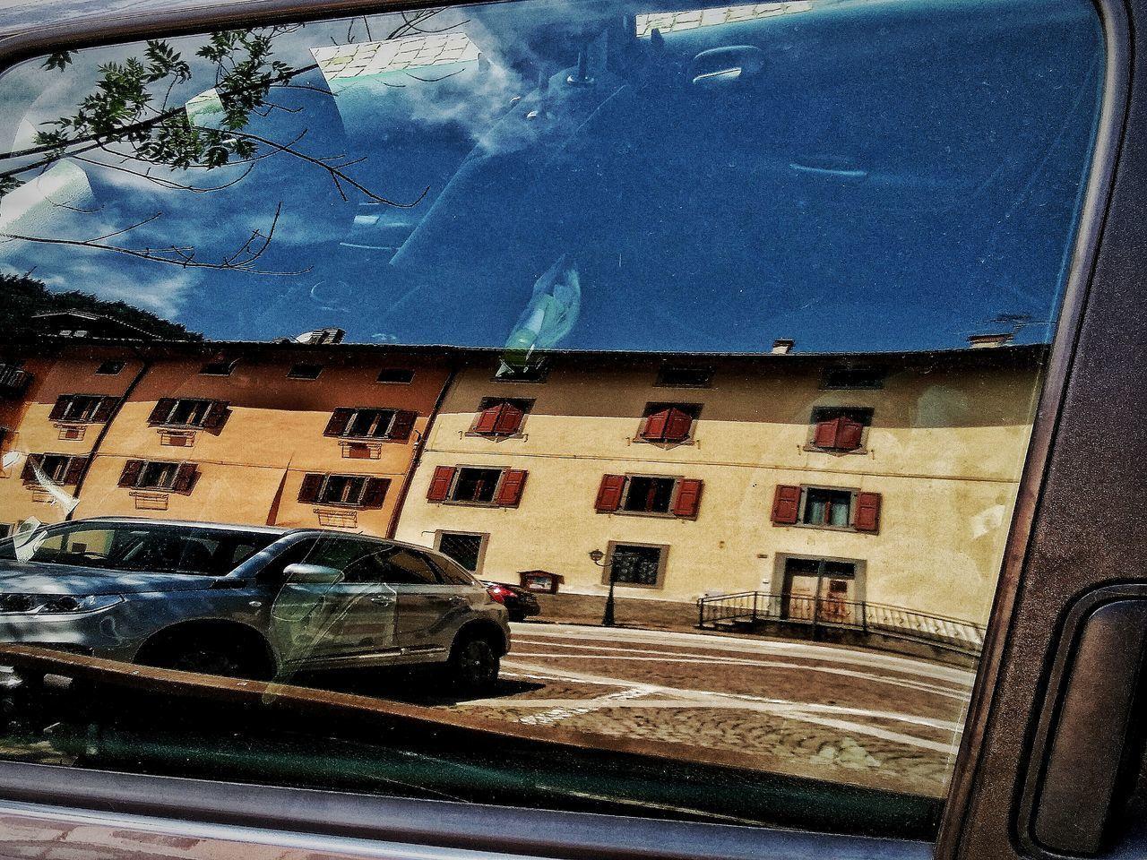 BUILDINGS SEEN THROUGH GLASS WINDOW OF CAR