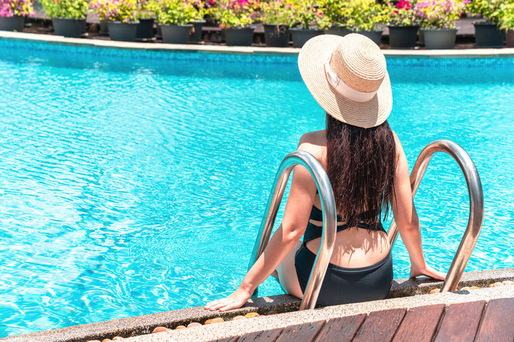 Rear view of woman sitting in swimming pool