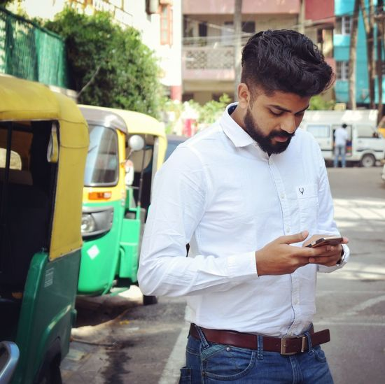 Man Using Mobile Phone While Standing On Street In City