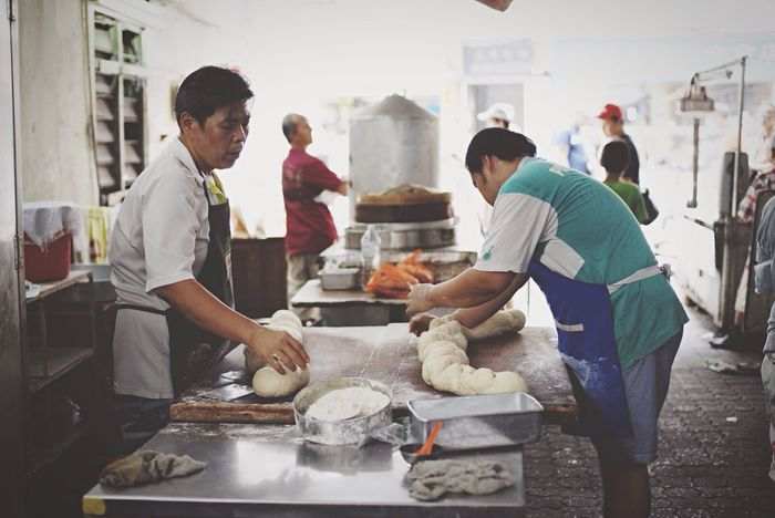Two unidentified men kneading Cakoi or Youtiao dough prior to cutting into small pieces before frying them Food And Drink Establishment Food And Drink Occupation Preparation  Cakoi Youtiao Fry Frying Knead Kneading Dough Dough Flour Ingredients Kitchen Rolling Hardwork Hardworking Street Photography Streetphotography Kuala Lumpur Malaysia Street Vintage Light And Shadow Light