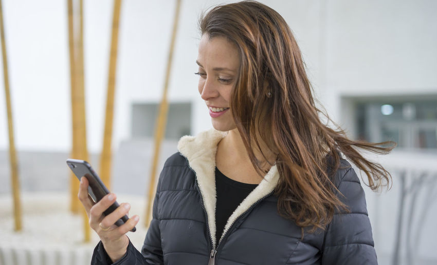 Close-Up Of Smiling Woman Using Mobile Phone
