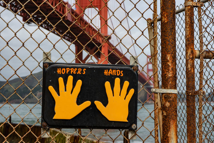 Metal Chainlink Fence Fence Safety Protection Security Text Western Script Communication Barrier Boundary Yellow No People Focus On Foreground Day Close-up Sign Outdoors Information Nature Golden Gate Bridge