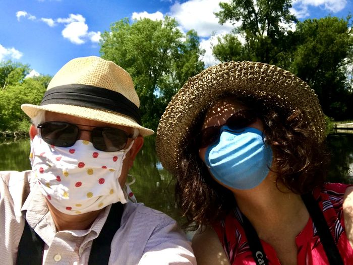 Portrait of man and a woman wearing masks while outdoors