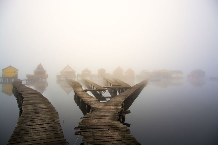 Piers leading towards stilt houses on lake during foggy weather
