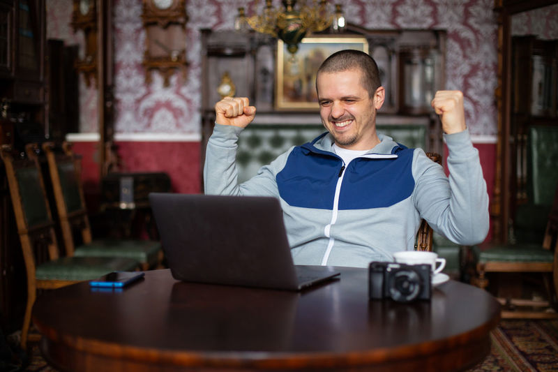 Man getting success. Freelancer happy with result. Smiling and looking in laptop. Laptop Computer Smiling Using Laptop Technology Wireless Technology Happiness Communication Front View Portrait Emotion One Person Looking At Camera Men Adult Connection Occupation Business Entrepreneur Freelancer, Success