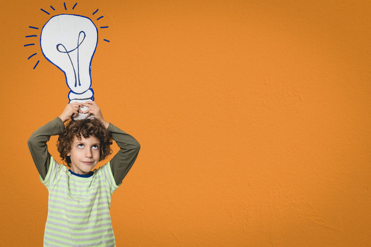 Kid keeping a cartboard light bulb in his head over a orange wall background. Comic like idea concept - room for text (copy space) Child Childhood Wall - Building Feature One Person Copy Space Front View Standing Males  Creativity Representation Arms Raised Real People Portrait Kid Boy Ideas Innovation Imagination Inspiration Intelligence Light Bulb Cardboard Close-up Copy Space Room For Text