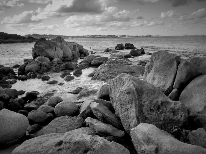 View Of Rocks In Sea Against Cloudy Sky