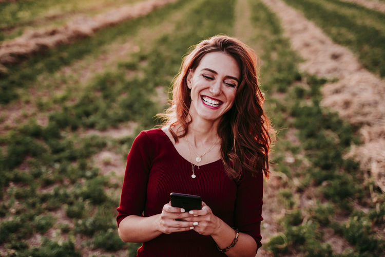 Happy woman using smart phone while standing on agricultural field