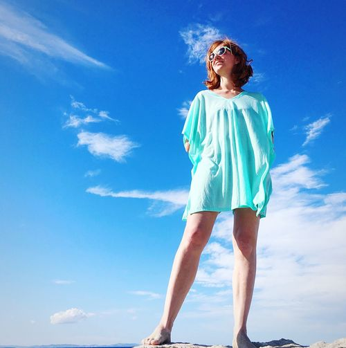 Low Angle View Of Woman In Sunglasses Standing Against Sky