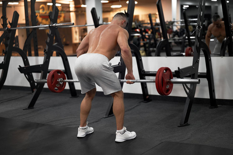 Rear view of shirtless man exercising at gym