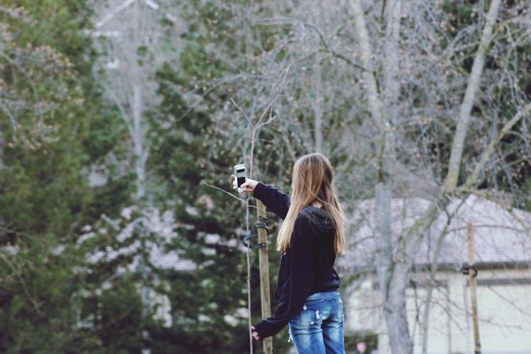 Woman photographing in forest