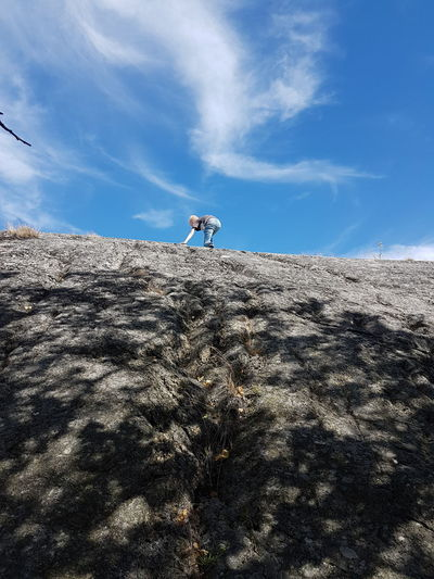 Low angle view of boy climbing on rock against sky