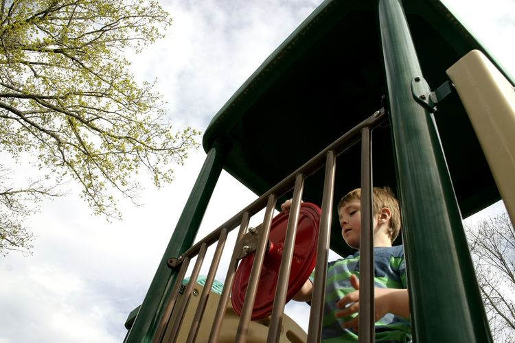 Low angle view of boys on slide against sky
