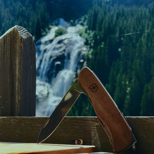 Pocket knife with waterfall Wood - Material Focus On Foreground No People Day Outdoors Water Close-up Nature Sky