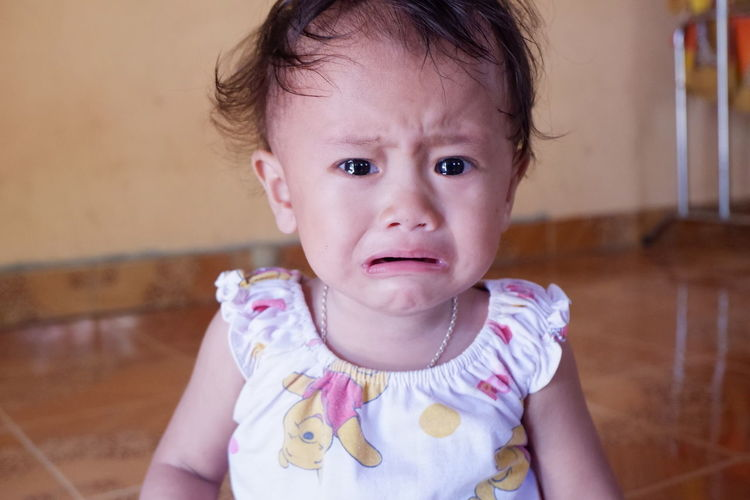 Portrait of cute baby crying at home