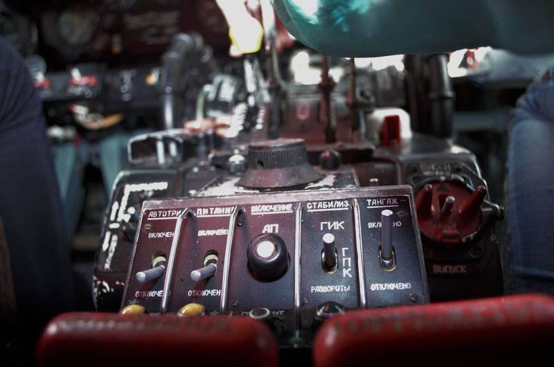 Knobs in control panel amidst men in vehicle