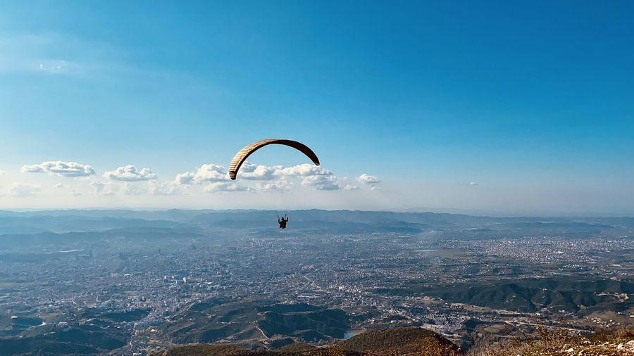People paragliding over tirana cityscape against sky