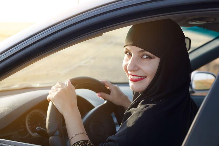Portrait of woman wearing hijab driving in car seen through window