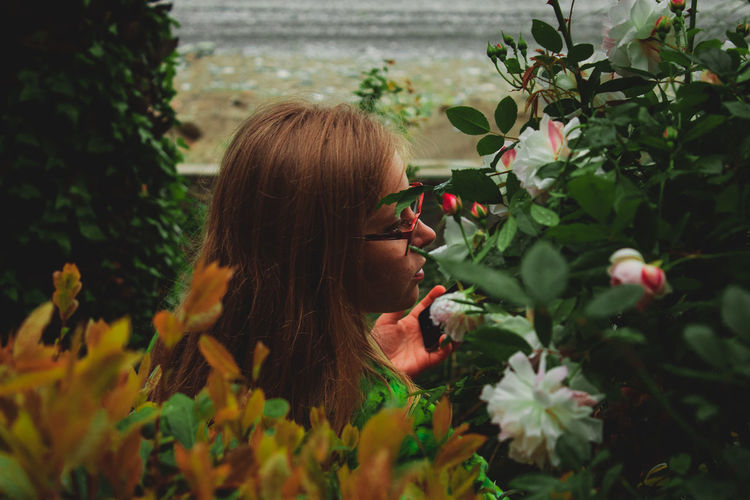 Woman with long hair by flowers