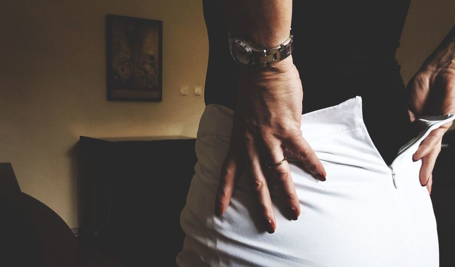 Midsection of woman removing white skirt at home