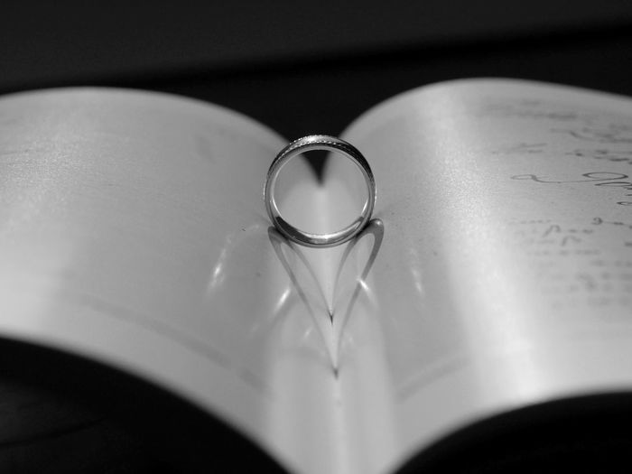 Ring With Heart Shape Shadow On Open Book